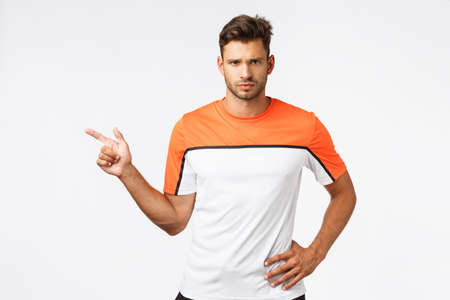 Upset serious-looking sad masculine bearded man in sports, football t-shirt, pointing left frowning disappointed, looking frustrated and questioned what happened, standing offended, white background