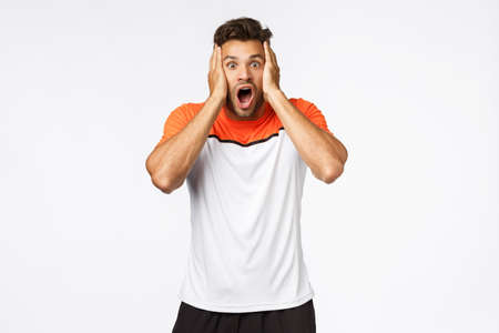 Shocked, speechless handsome mascular male athlete in sports t-shirt, gasping, drop jaw concerned and astonished, grab face from amazement, hear exciting news, standing white background