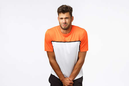 Poor young sportsman, football player in sports t-shirt, bending and grab groin area as feeling pain after player kicked ball, grimacing from painful feelings, squinting, suffering ache