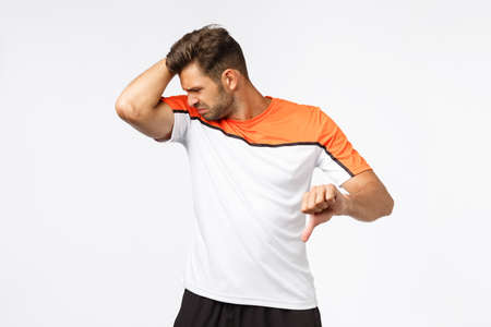 Guy feeling unconfident and upset as having problem with finding good deodorant. Masculine sportsman after workout raise arm and smell armpit, grimacing from disgust showing thumb-down displeased