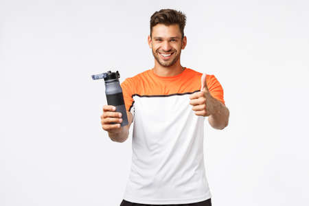 Handsome mascular and healthy fitness instructor recommend drink more water as key to good shape. Smiling good-looking sexy sportsman in activewear show thumb-up and hold sports bottle