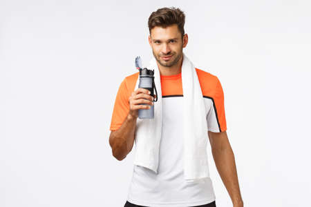 Handsome sportsman with bristle, wear activewear, towel over neck, holding bottle, drink water with satisfied smiling expression, finish good endurance practice, football player rest after match