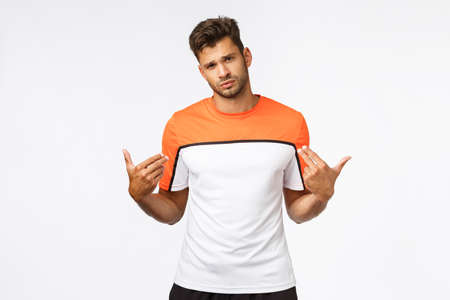 Handsome, sexy boastful sportsman in activewear, tilt head, look cheeky and determined camera, pointing himself as brag perfect body shape, pleased with well played football match, think he is best Stock Photo
