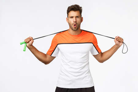 Handsome, energized sportsman ready for workout, hold jump rope behind neck, frowning sassy and look camera, folding lips grimacing sexy , invite join fitness training, prepare for maraphon