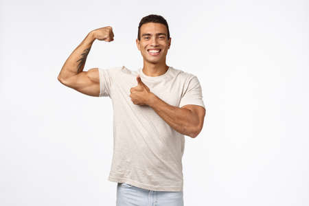 Handsome strong athletic sportsman in casual t-shirt, raise arm, tense muscle and proudly bragging good shape, big biceps, smiling pleased showing thumbs-up in approval and like, white background