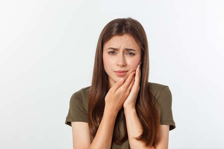Teen woman pressing her bruised cheek with a painful expression as if she is having a terrible tooth ache