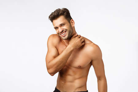 Sport, emotions and beauty concept. Handsome happy young sportsman with six-packs, touching neck and smiling camera with sexy expression, athlete posing naked torso, finish workout, white background Stockfoto