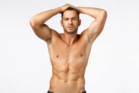 Sexy handsome, tanned masculine young man showing his perfect body, naked torso, raising hands up, touching head, squinting sassy and self-assured, workout, gain muscles, white background Stockfoto