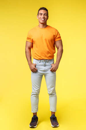 Vertical full-length studio shot young hipster guy with mascular body, standing orange t-shirt and white pants, hold hands in pockets, smiling camera pleased and confident, casual pose Stok Fotoğraf