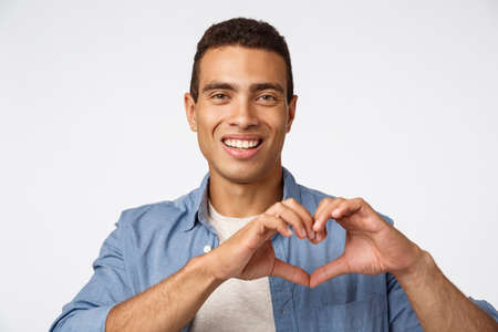 Love, cherity and affection concept. Charming young brazilian masculine man showing heart sign and smiling happy, make surprise dinner for valentines day, arrange christmas romantic night Stok Fotoğraf