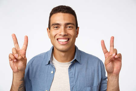 Cheerful young athletic man in casual outfit smiling happily, showing peace signs or quotation, standing carefree white background, play secret santa, ready bring joy coworkers holiday Stok Fotoğraf