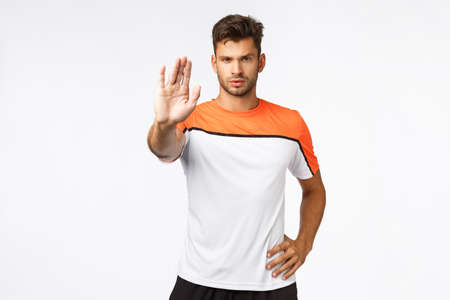 No tresspassing. Serious-looking determined young handsome male athlete in sportswear, t-shirt, pull arm forward in stop or hold motion, look determined and self-assured, forbid something Stock Photo