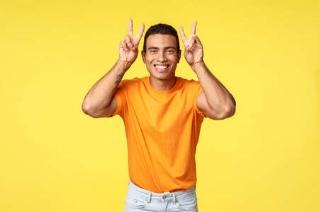 Happy, cute lovely hispanic boyfriend in orange t-shirt, showing peace or victory gesture over head, smiling silly, fool around try make tender expression to make girlfriend laugh, yellow background