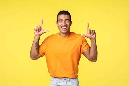 Happy cheerful young caucasian guy in orange t-shirt smiling pleased, pointing up laughing as promoting advertisement, give advice, recommend download app or shop at store, yellow background