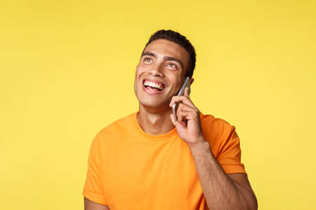 Conversation, modern people concept. Attractive friendly young man looking up and smiling cheerful as talking phone, discuss secret santa, christmas office party ith coworker via smartphone
