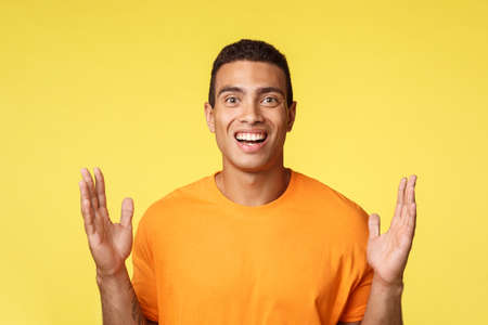 Attractive, excited caucasian man in t-shirt showing box or something big, spread hands near chest to form large object, explain something, discuss vast sales, having dialogue, yellow background 版權商用圖片