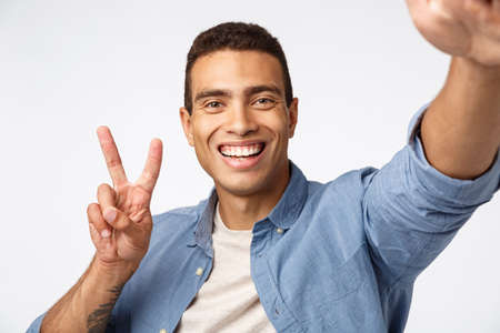 Happy and cheerful friendly man sending positivity, hold camera stretched hand and smiling at smartphone, taking selfie make peace sign, record vlog or talking to girlfriend online, white background
