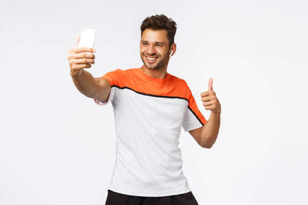 Good-looking masculine young sportsman wear wireless earphones, activewear, taking selfie on smartphone, show thumb-up and smiling pleased, recommend gym, promote healthy lifestyle and workout