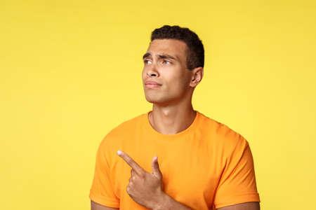 Étudiant de sexe masculin sceptique et peu impressionné faisant son choix, employé choisissant son lieu de travail, désapprouvant et n'aimant pas les sourcils, regardant pointant vers le coin supérieur gauche déçu, fond jaune