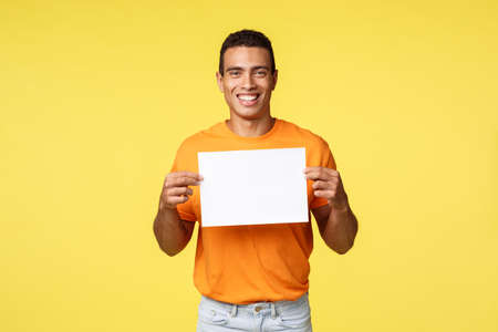 Happy smiling hispanic male in orange t-shirt, holding paper over chest and grinning as give advice, write favorite product or shop web site, give advice, recommend shopping spot, yellow background