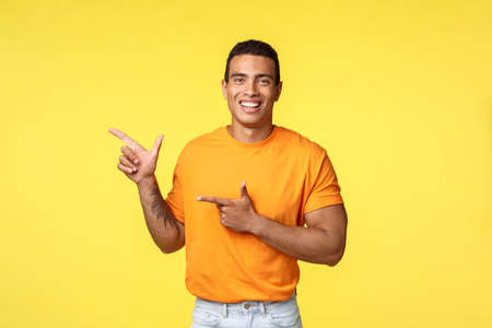 Cheerful modern man with tattooed arm, pointing left as promoting online store, invite guest join party, smiling joyfully, recommend try something, give advice what place visit, yellow background Stok Fotoğraf