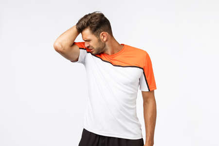 Young sportsman raise arm and smell stinky armpit after hard productive workout in gym, grimace, cringe from disgust, forgot use deodorant, cant find good product from sweat, white background