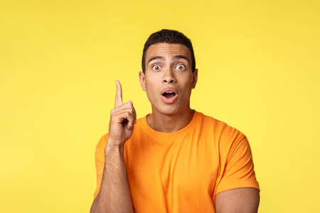 Got idea. Man say eureka as gasping and give advice, lighten with amazing idea, raise one finger in got-it gesture, stare camera talking to friend, standing yellow background excited
