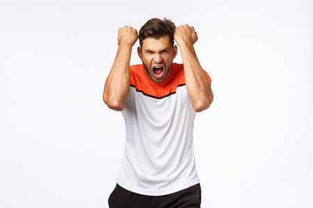 Motivation, sport and sportswear concept. Determined and confident handsome sportsman, raising hands, fist pump encourage hismelf with shout as workout, bodybuilder during gym training session