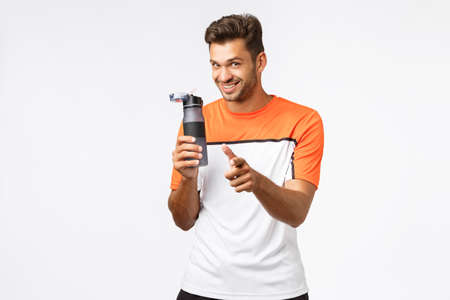 Cheerful handsome smiling sportsman in activewear pointing camera and grinning, holding bottle, encourage gym members drink more water after workout, training session, stand white background Stock Photo