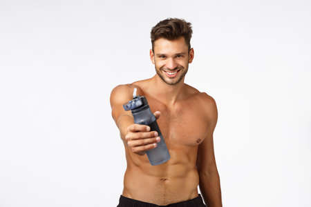 Sexy handsome and self-assured sportsman give you water bottle drink and refresh, smiling confident, posing naked torso. Shirtless sassy athlete give drink after productive fitness workout