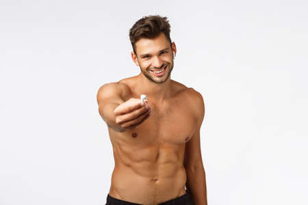 Sexy attractive smiling young shirtless sportsman give you one wireless earphone listen music together during workout, fitness training, grinning joyfully, standing naked torso show perfect body