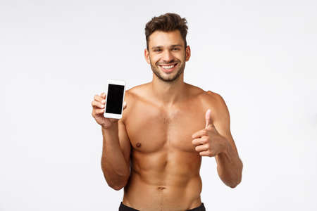 Handsome shirtless concept give good advice, suggest download workout fitness tracker app. Sexy sportsman with naked torso, perfect body shape, smiling pleased, holding smartphone, show thumbs-up