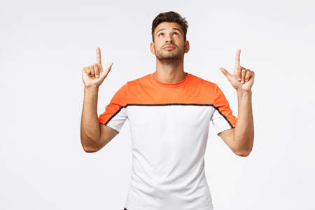 Handsome caucasian bearded sportsman, masculine guy in activewear looking up, pointing top advertisement, reading curious promo, intrigued with product advertisment, white background Stock Photo
