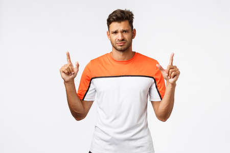 Gloomy, disappointed handsome bearded guy in activewear feeling upset, pointing up, frowning as showing something frustrating, frowning, grimacing as complaining, standing white background Stock Photo