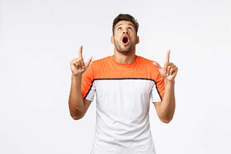 Guy drop jaw from amazement, see stunning great product on top advertising. Masculine handsome man in activewear raise head, gasping wondered and excited, pointing upwards, white background