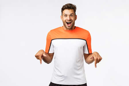 Excited, astonished handsome male in sports t-shirt, amazed receive cool new trainers for christmas, pointing down enthusiastic, smiling from happiness and joy, standing white background Stock Photo