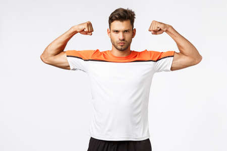 Strong sassy and handsome young sportsman, taking care body, wearing activewear, sports t-shirt, showing muscles, raise hands and brag biceps, frowning look determined and masculine Stock Photo
