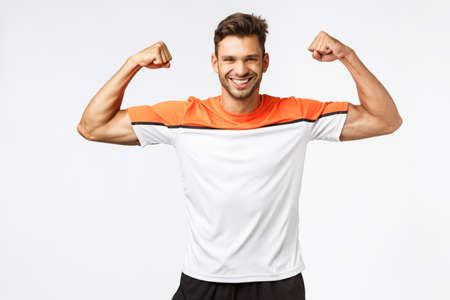 Strong happy, enthusiastic handsome bearded man in sports t-shirt, activewear, raise hands and brag with muscles, strong biceps, perfect body shape, smiling delighted after good workout in gym Stock Photo