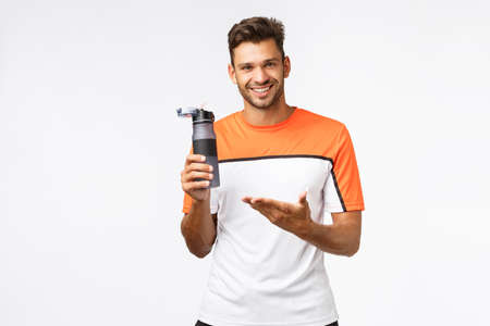 Fitness instructor holding water bottle and pointing at it as recommend drink after workout. Handsome mascular man share his knowledge about diet and healthy lifestyle, standing white background Stock Photo