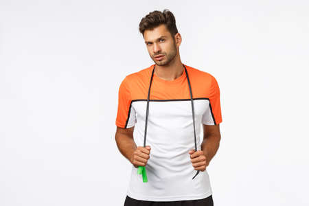 Sassy handsome sportsman, look cheeky and focused, fitness instructor watching client doing exercise in gym, waiting with jump rope, getting fit, lead active and healthy lifestyle with sport