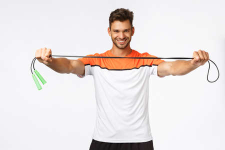 Handsome energized fitness instructor giving jump rope, instruct how lead active and healthy lifestyle, smiling daring, ready for gym training, bought membership to get in shape, white background
