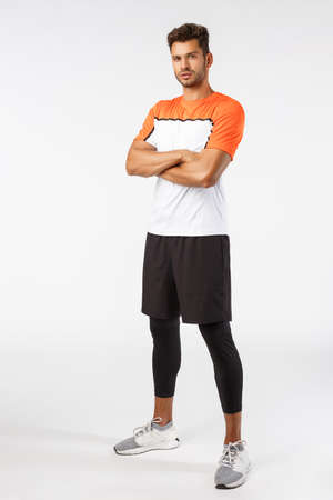 Confidence, sport and fitness concept. Vertical shot good-looking bearded handsome young sportsman in activewear, cross arms over chest, look determined and serious, ready win match