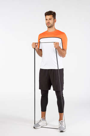 Vertical shot serious-looking focused handsome male athlete in sportswear, shorts, t-shirt trainers, stretch band loop with feet and hands, look serious, prepare for productive workout training