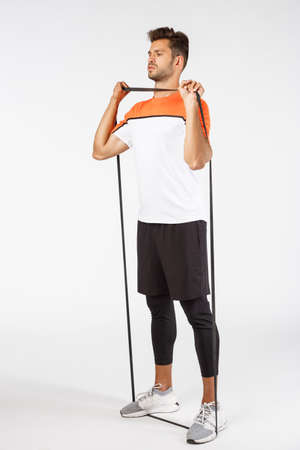 Vertical, full-length sportsman workout with loop band, stretch resistance rope with feet and arms, look sideways determined and serious, fitness training. Football male athlete prepare for match