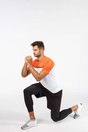 Endurance, workout and fitness concept. Motivated, serious-looking sportsman in activewear, bend on knee, create tension with clenched arms, look focused, workout over white background, full-length