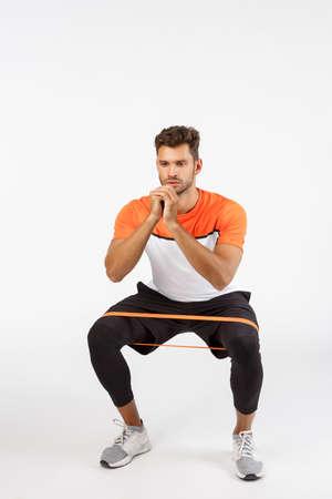 Lo sportivo di bell'aspetto motivato e concentrato esegue squat con corda di resistenza, allungando l'attrezzatura piegando i piedi lateralmente, sedendosi e stringendo le braccia insieme per essere in buona forma, concetto di allenamento