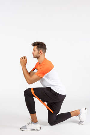 Vertical profile shot sportsman perform squats as secure resistance rope between legs, stretch loop with knee, clench arms together, trying get fit during active training session, white background