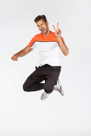 Frecher, glücklicher attraktiver junger bärtiger männlicher Sportler in Activewear, springt und zeigt Friedenszeichen in der Luft, zwinkert freudig, drückt Positivität aus, macht Spaß beim Training und macht Sport, weißer Hintergrund