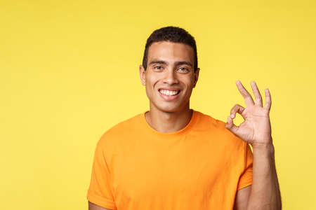 Guy approves your perfect choice. Cheerful good-looking man in t-shirt showing okay gesture, like something good, smiling as agree, accept nice product, share opinion, feeling healthy and fine