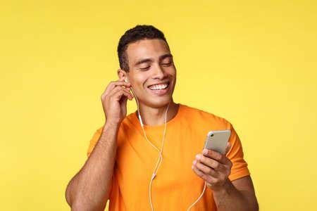 Allegro giovane maschile sorridente in t-shirt arancione, tenendo in mano lo smartphone, chiacchierando ascoltando musica o guardando video in cuffia, ricevuto un messaggio vocale e ridendo su di esso, sfondo giallo Archivio Fotografico